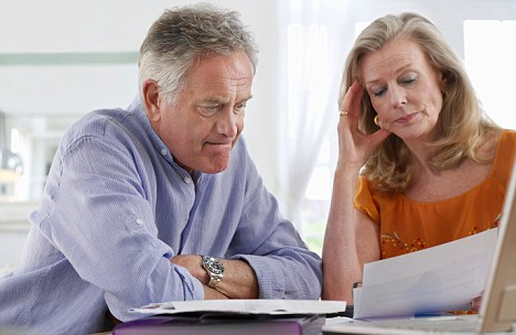 Senior couple looking at bills, sitting at dining table. Image shot 2009. Exact date unknown.